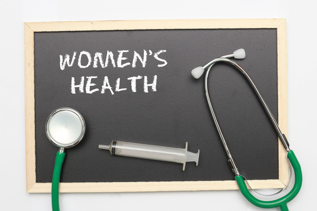 WOMEN'S HEALTH concept with stethoscope and syringe